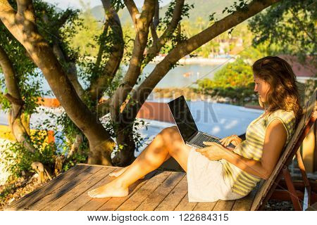 Young woman with laptop sitting on sunbed in the resort.