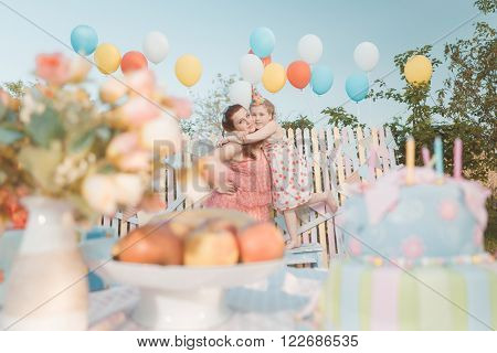 Mother holding her baby girl in birthday hat