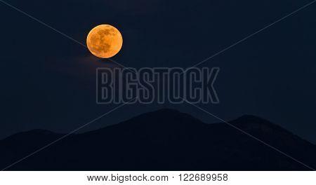 Full orange moon rising over the mountains