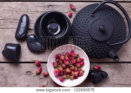 Dry rose tea in bowl and traditional asian tea set on aged wooden background. Selective focus is on tea.