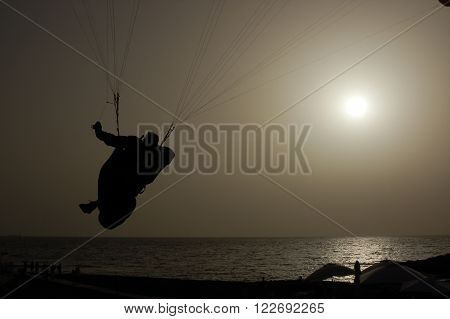 Paragliding Backlit Flying Over A Beach In Tenerife