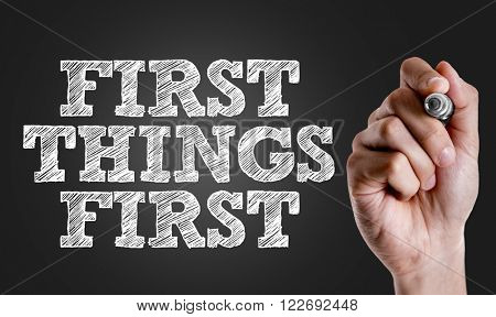 Hand writing the text: First Things First