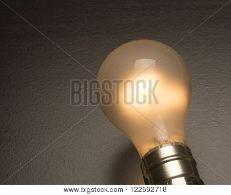 Tungsten light bulb for home use on dark background.