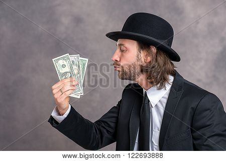 young businessman with bowler hat in black suit showing money