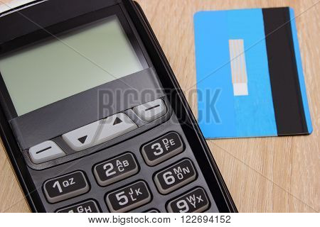 Payment terminal with credit card on wooden desk credit card reader paying using credit card finance and banking concept