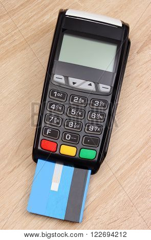 Payment terminal with credit card on wooden desk, credit card reader, paying using credit card, finance and banking concept