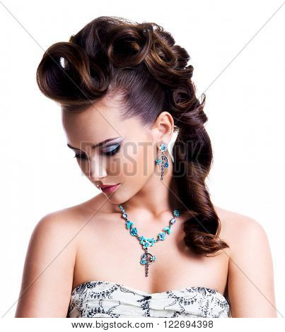 Profile portrait of a beautiful young woman with creative hairstyle  and bright colored eye makeup. Fashion model wear blue earring and necklace - isolated on white