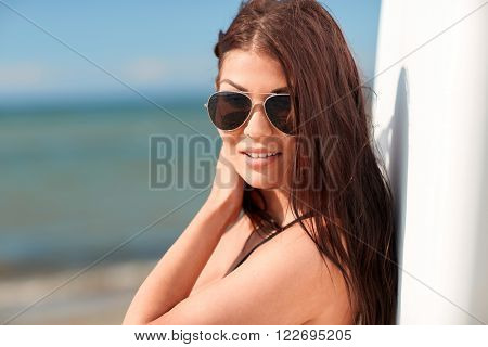summer vacation, travel, surfing, water sport and people concept - young woman in sunglasses with surfboard on beach