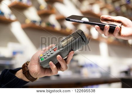Woman paying with NFC technology on mobile phone in shop