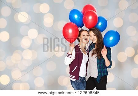 people, friends, teens, holidays and party concept - happy smiling pretty teenage girls with helium balloons over lights background