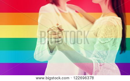 people, homosexuality, same-sex marriage and love concept - close up of happy married lesbian couple dancing over rainbow flag stripes background
