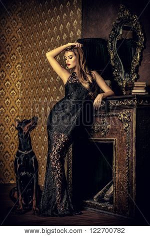 Beautiful lady with her dog in a room with luxurious classic interior. Fashion.