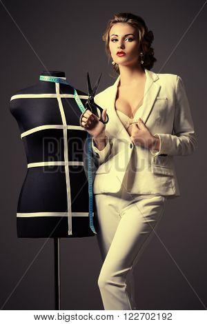 Portrait of a stylish woman  fashion designer. Studio shot over dark background.