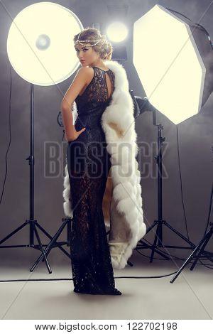 Stunning beauty model posing at studio in light flashes. Professional fashion model. Celebrity. Full length portrait.