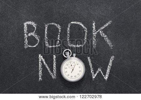 book now watch phrase handwritten on chalkboard with vintage precise stopwatch used instead of O