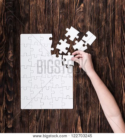 hand collecting white puzzle on brown background