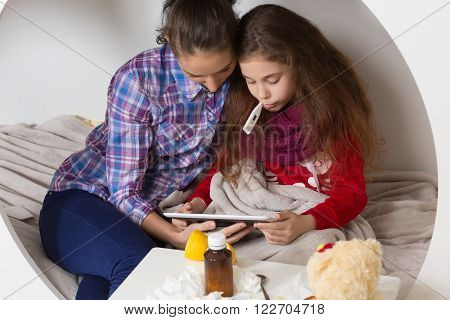 Fever, cold and flu concepts. Mother and her daughter looking into tablet PC. Sick lady measuring temperature with thermometer in mouth.