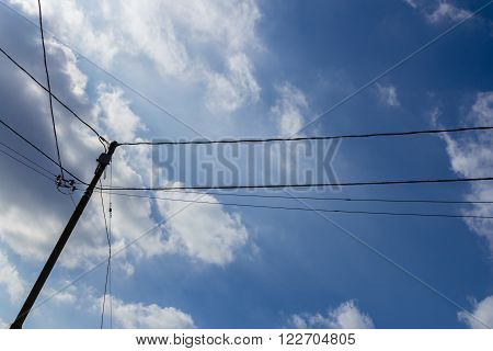 Old wooden pole with cables for telephone and power services with blue and cloudy sky