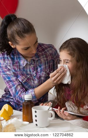 Fever, cold and flu concepts. Little girlblowing her nose in tissue while her mother sitting near her and helping her.