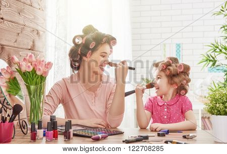 Happy loving family. Mother and daughter are doing hair, manicures, doing your makeup and having fun. Mother and daughter sitting at dressing table at house.