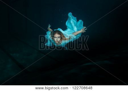 A woman in a white dress as a mermaid swimming under water.