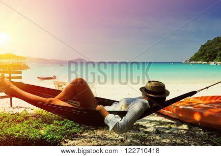 Woman in hammock on tropical beach at Perhentian islands, Malaysia