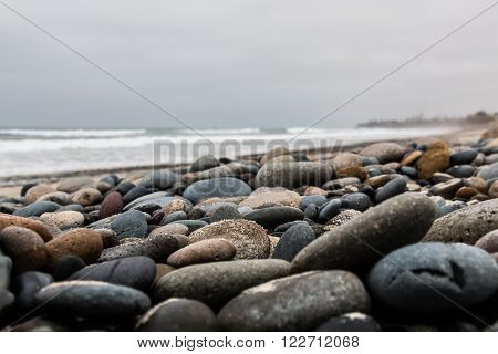 Low angle of stones scattered over the beach at South Carlsbad State Beach in San Diego, California.