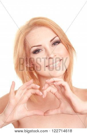 Smiling blonde woman making heart shape by hands over white. Closeup portrait of beautiful young girl 20-25 years old posing. Looking at camera. Isolated.
