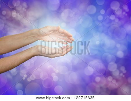 Sensing subtle healing energy - female hands held gently cupped demonstrating energy sensing  on a soft purple blue bokeh background with plenty of copy space