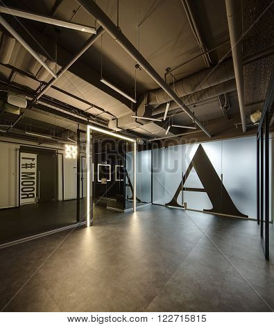 Loft style interior. Mirrored walls with reflected parts of the room on it. Between the walls there is a corridor with door on right side. Start of corridor allocated by luminous frame. There is a luminous pointer on the wall on the left. The doors with l