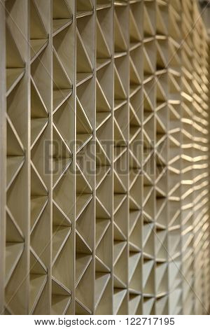 Ornamental light wooden partition. The ornament consists of triangles. Vertical.