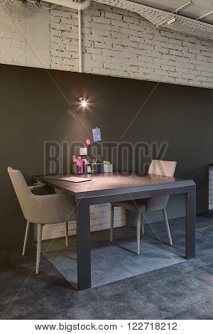 Dark table with two chairs on the sides on a background of a dark board on the white brick wall. There is a lamp and stickers on the board. On the table there is a laptop, holders with pens and a pink robot, plant in a pot. On the floor there are gray til