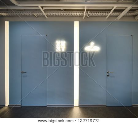 Interior in a loft style. Light blue wall with two doors. There are luminous pointers between doors on the wall. There are two vertical narrow lamps in the recesses in the wall. One lamp is between doors and second is left side of the left door. At the to