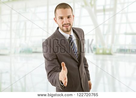 young businessman in suit offering to shake the hand at the office