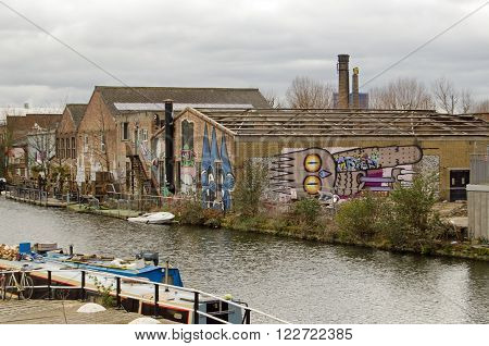 HACKNEY LONDON - MARCH 19 2016: Derelict industrial buildings covered in graffiti on Fish Island overlooking the River Lee Navigation in Hackney London. The area is now trendy and full of artists and hipsters.