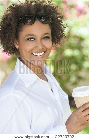 Beautiful young mixed race black African American woman smiling wearing sunglasses drinking a takeaway cup of coffee outside