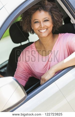 Beautiful young happy smiling mixed race black African American woman driving a car