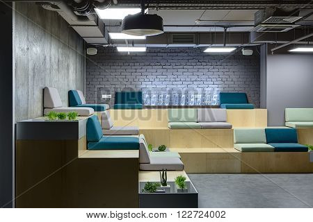 Wooden benches with multi-colored seats. Seats are made up of pillows. At the back on bench there is a digital clock which made from the transparent rectangles. Left wall is from concrete and back wall is from brick. There are several niches on the benche