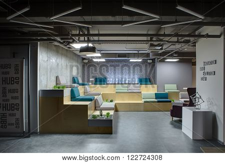 Room in a loft style with big zone with wooden benches with multi-colored seats. Benches are made in the form of steps. Seats are made up of pillows. At the back on bench there is a digital clock which made from the transparent rectangles. At the benches