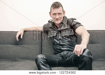 man wearing black fetish leather clothes and sitting on couch
