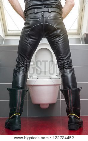backside of man wearing black leather fetish clothes standing at toilet