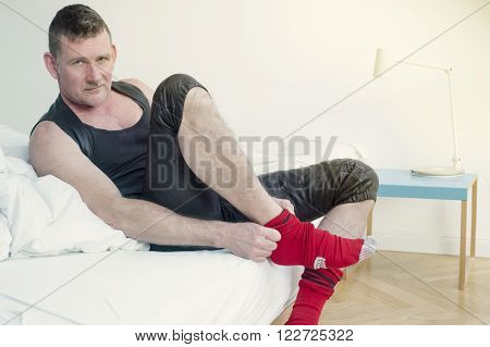 man in fetish leather gear sitting on bed and putting on his socks