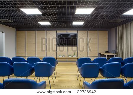 Lecture room in a coworking. There are a lot of blue chairs. Background wall is dark gray with wooden panels and TV on it. There are plants in the pots under the TV. On the left there is a white wall with a part of glass door. On the right there is a wood