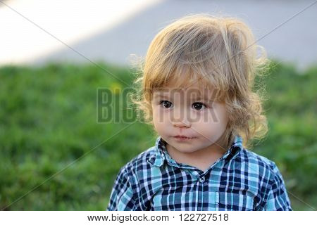 Portrait of cute adorable small smart serious boy child with blonde hair in stylish blue checkered shirt outdoor on summer green grass background, horizontal picture