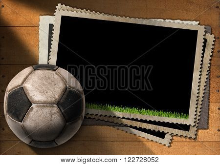 A stack of old vintage and blank photo frames with an old soccer ball (football). On a wooden background