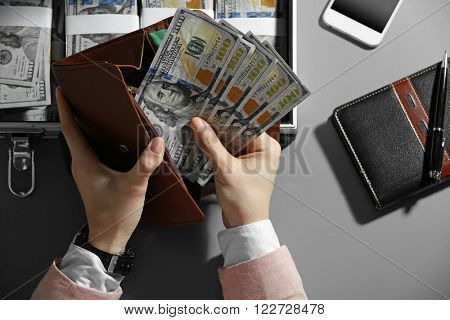 Businesswoman with wallet and case full of money