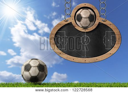 Oval blackboard with a football field (Usa Soccer) and an old ball. Hanging from a metal chain on a blue sky with clouds and sun rays