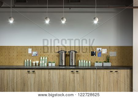 White wall with wooden panels with stickers on them. Below there is a rack with wooden cases under it. On the rack there are two chromium-plated thermoses, a lot of cardboard cups and several plants in the pots. At the top there are four white lamps in th