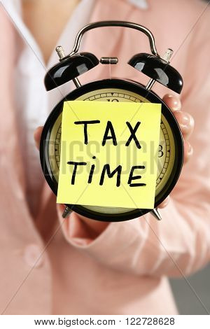 Woman in pink suit holding alarm with tax time inscription, close up