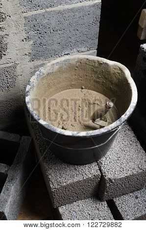 A bucket with a solution and a trowel, close-up